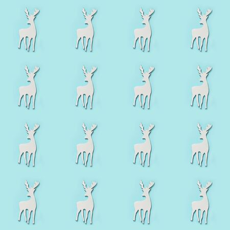 White Christmas reindeer with antlers on blue. Seamless pattern. Flat lay. New Year texture. Top view.