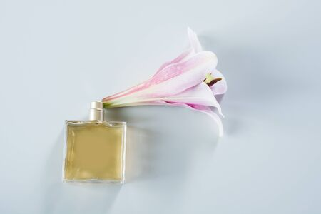 Luxury bottle of perfume with fresh lily flowers on color blue background. Space for text, top view.