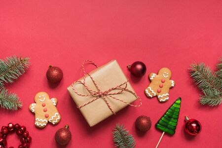 Christmas border of handmade gift boxes, wooden diy decor, evergreen branches, gingerbread cookies on red. Stok Fotoğraf