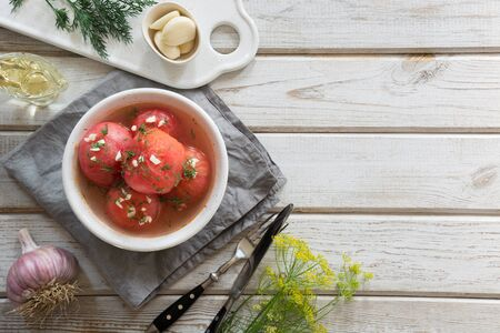 Marinated peeled tomatoes with garlic and dill, fresh ready to serve.