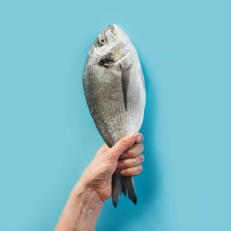 Female hand with dorado fish tail on blue paper as color of sea. Stok Fotoğraf