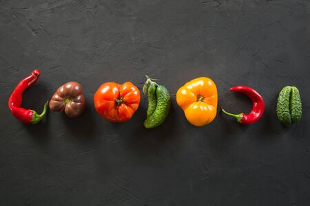 Oddly shaped colorful tomato, pepper, cucumber on black.