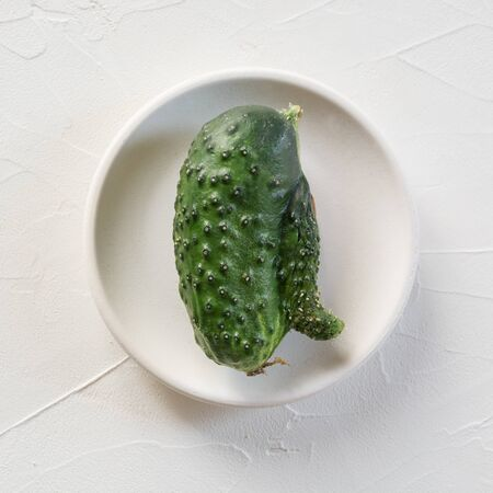 Oddly shaped cucumber on white plate. Concept of organic vegetable. Stok Fotoğraf