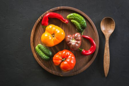 Oddly shaped organic colorful tomato, pepper, cucumber in wooden tray on black concrete. Concept of organic vegetables.