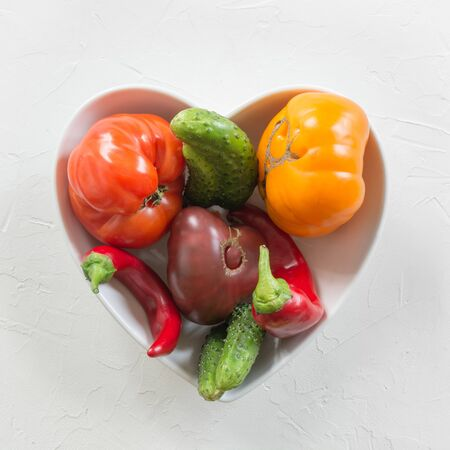 Oddly shaped organic colorful tomato, pepper, cucumber in dish as heart on white concrete. Concept of organic vegetables. View from above. Stok Fotoğraf