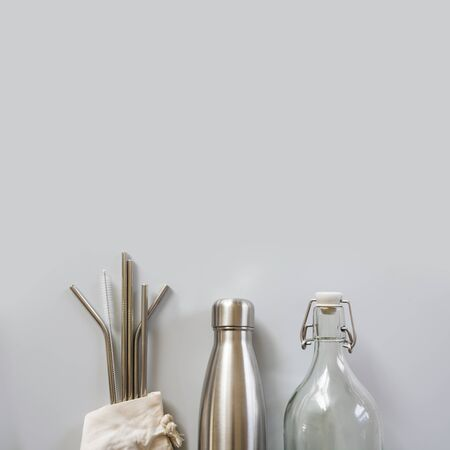 Eco natural metallic straws, bottle with cotton bag on grey. Sustainable lifestyle concept. Zero waste, plastic free. Pollution environment.
