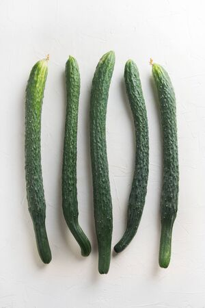 Oddly shaped five long cucumbers. Concept of organic vegetables. Close up.