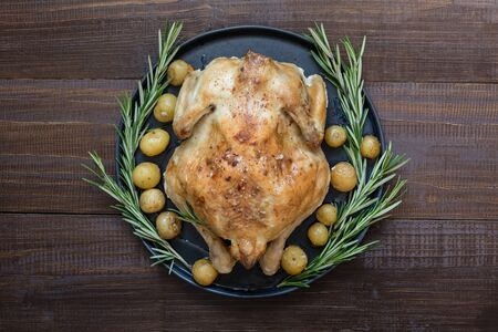 Traditional roasted turkey with rosemary on wooden table. Top view. Thanksgiving day.