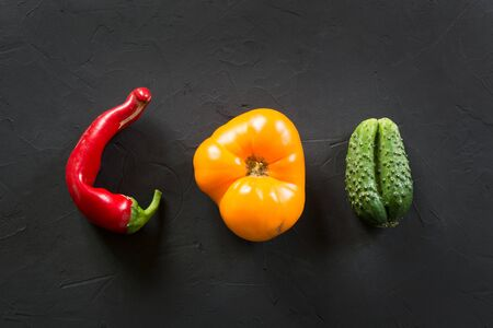 Oddly shaped organic colorful tomato, pepper, cucumber on black.