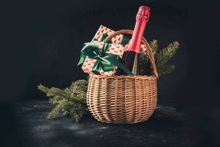 Christmas gift hamper with champagne and gift with green bow on black.