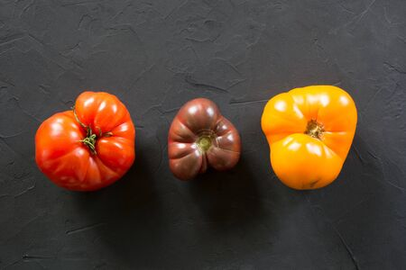 Oddly shaped organic colorful tomatoes  on black concrete. Concept of organic vegetables. Stok Fotoğraf