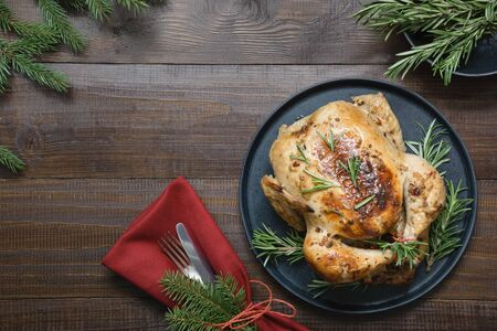 Traditional Christmas roasted turkey with spices and rosemary on wooden table with decor of evergreen branches. Top view. Space for text. Xmas.