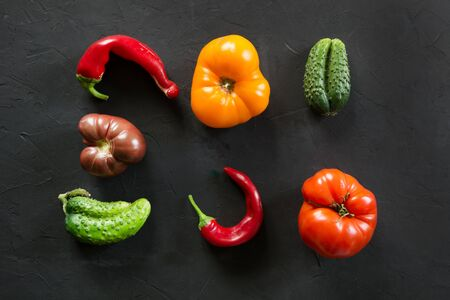 Oddly shaped organic colorful tomato, pepper, cucumber on black concrete. Concept of organic vegetables.