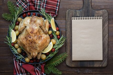 Traditional Christmas roasted turkey with spices and rosemary on wooden table. Blank for recipe or menu. Top view. Space for text. Xmas.