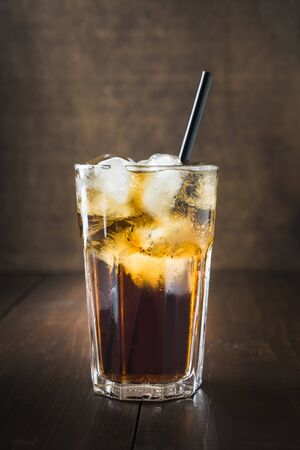 One glass of refreshing drink with ice on dark wooden board. Close up. Stok Fotoğraf