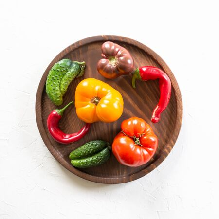 Oddly shaped organic colorful tomato, pepper, cucumber in wooden dish on white. Concept of organic vegetables. View from above.