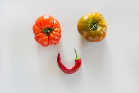 Oddly shaped tomatoes and hot pepper as smiley face on grey. Concept of organic vegetables.