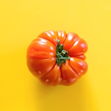 Oddly shaped ripe tomato on yellow. Concept of organic vegetables.