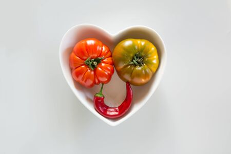 Oddly shaped ripe tomatoes and hot pepper as smiley face on grey. Concept of organic vegetables.