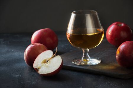 Glass with Calvados brandy and red apples on black. Close up.