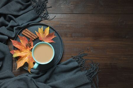 Autumn composition with cup of coffee, colorful dry leaves, grey scarf on dark wooden board. View from above. Space for text.
