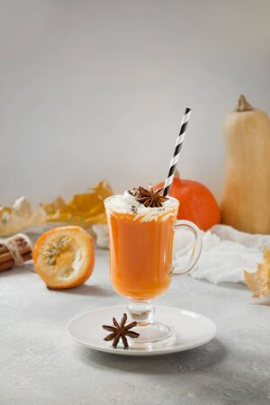 Pumpkin drink with cream and anive star on light grey. Autumn, fall or winter hot drink. Cozy healthy beverage.