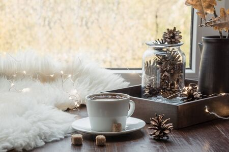 Fall cozy still life on windowsill at home interior. Cup of coffee at home warm fluffy furskin. Hygge concept. Creativity and inspiration.