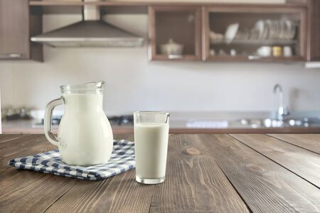 Glass of fresh milk and jug on wooden tabletop with blur kitchen as background. Space for text or display product.