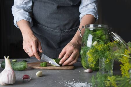 Woman cutting cucumbers for pickle with garlic and dill in glass jar. Rustic dark style. Cooking. Close up. Stok Fotoğraf
