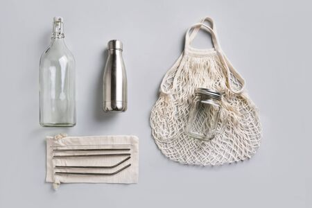 Reusable glass and metal bottle, mesh bag for zero waste lifestyle on grey background. Free plastic. Stock fotó