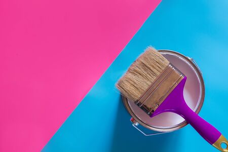 Purple brush with open can of white paint on blue and pink neon background. Trend repairs concept. Foto de archivo