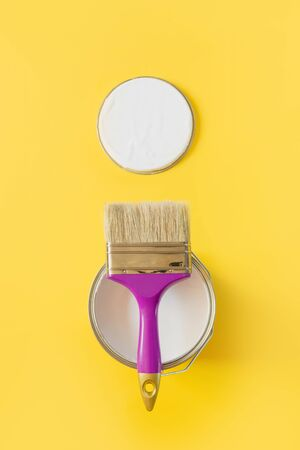 Purple brush with open can of white paint on yellow background. Trend repairs concept. View from above.