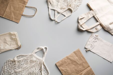 Reusable mesh, cotton and net bag for zero waste lifestyle on grey background. Zero waste shopping. Space for text.