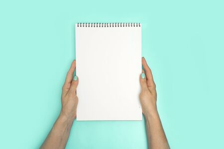 Woman hands hold sketchbook with white page for text.
