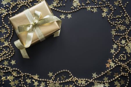 Borde of luxury golden gift box with gold stars on shine black background. Christmas pattern. Flat lay. Top view. Festive backdrop. Xmas. Foto de archivo