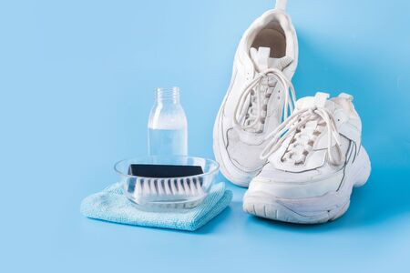 Scarpe da ginnastica bianche sporche con pennello e strumento speciale per pulirle su sfondo blu. Concetto di lavaggio. Cura regolare delle scarpe da ginnastica. Spazio per il testo.
