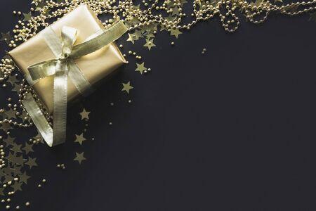Border of luxury golden gift box on black background. Christmas present. Flat lay. Top view. Xmas. 免版税图像 - 131628360