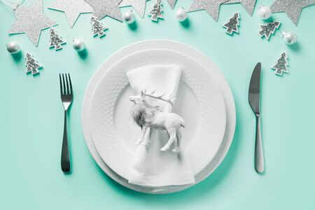 Christmas white winter table setting with reindeer on neo mint background. Top view. Xmas dinner.