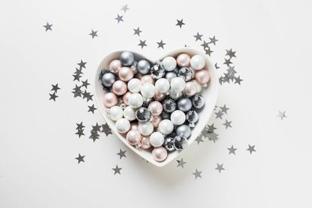 Christmas white, pink, grey silver balls in plate shape of heart decorated confetti stars on pink background. Top view. Xmas concept. Love holiday New Year. Stok Fotoğraf