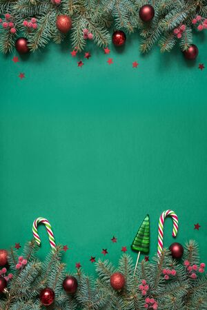 Christmas tree branches, red glass balls on green with copy space. Top view. Holiday Xmas card. Happy New Year. Stock Photo
