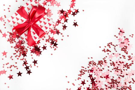 Christmas present with red bow on white background with red stars and sparkles. Xmas banner. Happy New Year. Flat lay style.