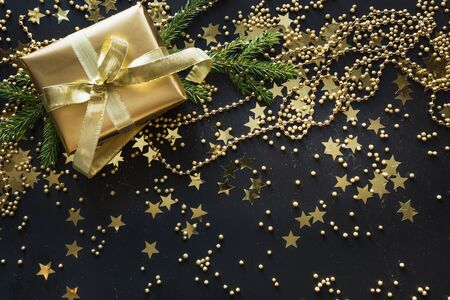 Border of golden gift box with confetti stars on black background. Christmas pattern. Flat lay. Top view. Festive backdrop. Xmas. Happy New Year. Boxing day. Stockfoto