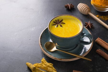 Cup of ayurvedic golden turmeric latte milk with curcuma powder and anise star on black. Close up.