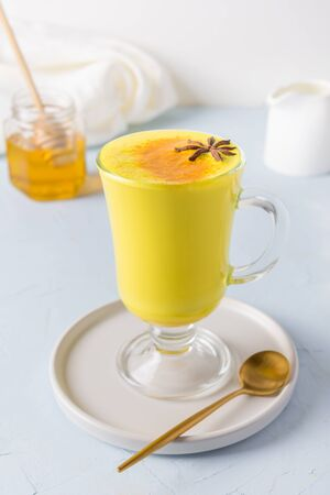 Glass of ayurvedic golden turmeric latte milk with honey and curcuma on white. Natural detox beverage. Close up. Vertical shot. Trendy Asian healthy drink for immunity with spices for vegans. 版權商用圖片
