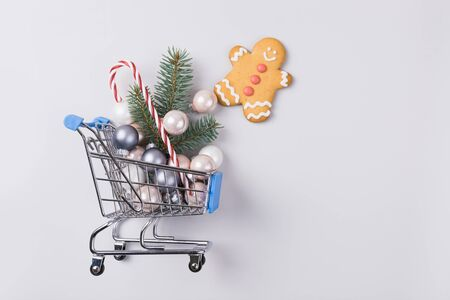 Christmas sale, shopping concept - trolley cart full of balls and xmas tree. Preparation to holiday and boxing day. Top view. Space for text.