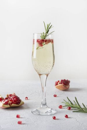 Pomegranate Christmas cocktail with rosemary, champagne, club soda on grey table. Xmas Holiday drink. Stock fotó