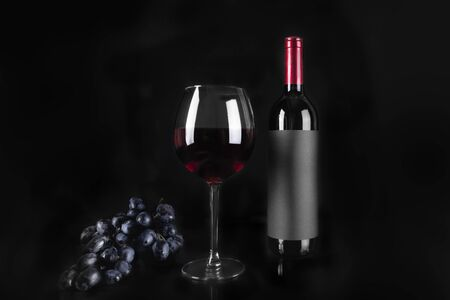 Wine glass of red wine and bottle, bunch of grapes on black background.