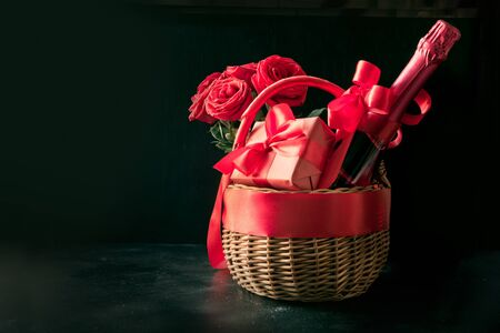 Valentines day gift hamper, bouquet of red roses, bottle of champagne on black table. Close up. Horizontal format. Space for wishes.
