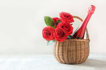 Valentines day gift hamper, bouquet of red roses, bottle of champagne on white. Close up. Horizontal format. Space for wishes. Romantic gift.