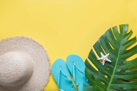 Female beach straw sunhat, outfit, flip flops, tropical monstera on yellow. Top view. Summer travel concept. Top view and space for text. 免版税图像